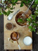 Faire du café dalgona coréen à la mode à l'extérieur avec tous les ingrédients sur une planche de bois à l'extérieur par une journée ensoleillée