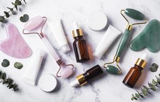 des produits cosmétiques, des tubes de crème, des huiles essentielles et un rouleau pour le visage photo