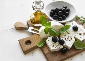 Ricotta fraîche aux feuilles de basilic et olives sur une planche de bois photo
