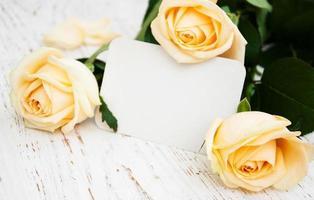 roses avec une carte sur un vieux fond en bois