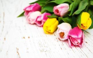 Bouquet de tulipes roses et jaunes sur fond de bois photo