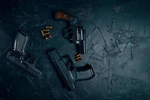 trois armes à feu et balles sur tableau noir photo