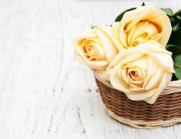 Panier avec des roses sur une vieille table en bois photo