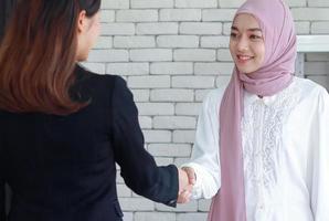 femmes musulmanes se serrent la main pour saluer leurs collègues