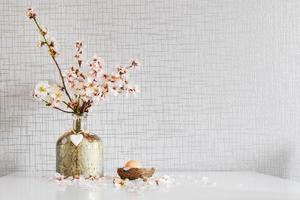 Vase avec des marguerites blanches colorées fraîches dans un vase, décoration d'oeufs de Pâques sur table blanche