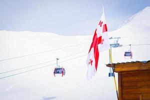 gudauri, georgia 2020 - drapeau géorgien avec panorama de gudauri et remontées mécaniques de la cabine de ski photo