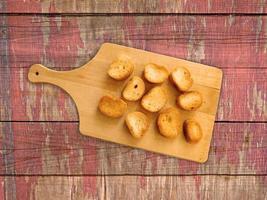 Tranches de pain grillé sur une planche à découper en bois sur un fond de table en bois photo