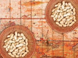 Arachides entières dans un bol en osier sur un fond de table en bois photo