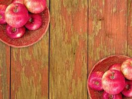 Pommes rouges sur une plaque en osier sur un fond de table en bois photo