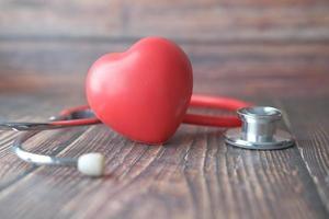 symbole de forme de coeur et stéthoscope sur fond de bois photo
