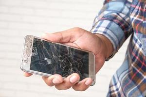 homme tenant un écran de téléphone fissuré