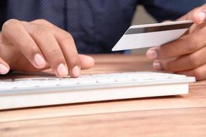homme tenant une carte de crédit et en tapant sur le clavier photo