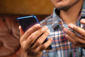 jeune homme utilisant un téléphone intelligent bleu photo
