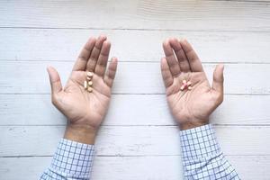 homme avec des pilules à deux mains