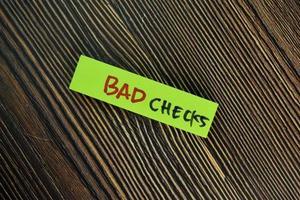 Mauvais chèques écrits sur pense-bête isolé sur table en bois