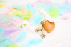 oeuf de pâques et plumes d'oiseaux colorés sur fond clair photo