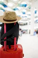 Chapeau de paille accroché sur la poignée de bagage rouge avec fond de voyage flou