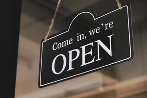 Panneau ouvert accroché à la porte vitrée d'un petit commerce