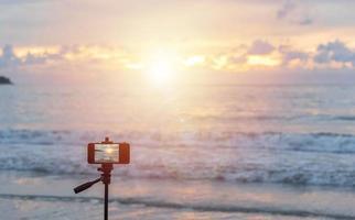 Quelqu'un voyageant à la plage de Patong, Phuket, Thaïlande avec un téléphone mobile sur un trépied en attendant le coucher du soleil pour prendre une bonne photo