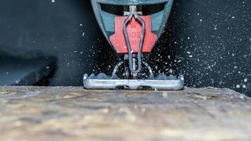 Close up de scie sauteuse électrique coupant un morceau de bois photo
