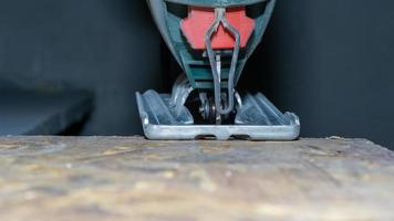 Close up de scie sauteuse électrique coupant un morceau de bois