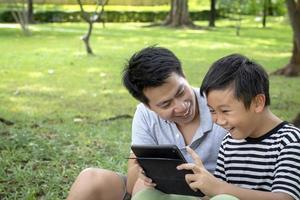 père et fils à l'aide d'une tablette à l'extérieur