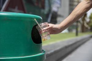 personne recyclant un gobelet en plastique photo