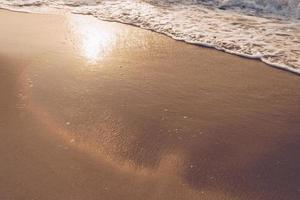 Vue de dessus des éclaboussures de sable et d'eau de mer avec espace copie sur une plage d'été tropicale propre photo