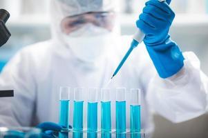 scientifique, laissant tomber un liquide dans des tubes à essai photo