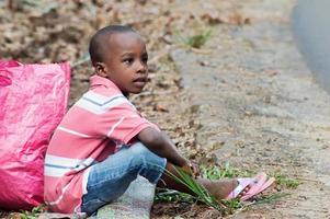 enfant assis par terre et à côté de lui un sac