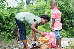 Jeune femme en plaçant le panier vers le bas et en aidant l'enfant debout à côté d'elle lors d'un pique-nique photo