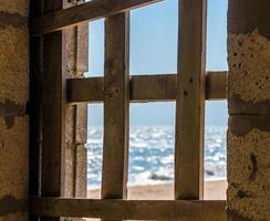 vue sur le bord de mer à travers une fenêtre barricadée