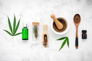 Bouteille en verre d'huile de chanvre avec un mortier blanc et des feuilles de chanvre mis en place sur un fond de béton, concept d'aromathérapie