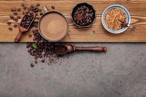 Grains de café torréfiés avec une tasse de café sur un fond de pierre sombre photo