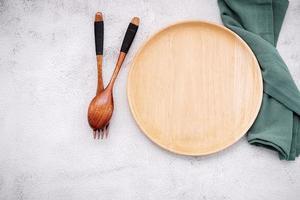 Assiette en bois vide et une serviette en lin vert avec une cuillère en bois et une fourchette sur un fond de béton blanc photo