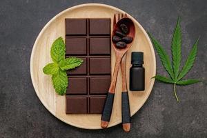 Feuille de cannabis avec du chocolat noir, des feuilles de plantes et des ustensiles en bois sur un fond de béton foncé