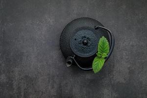 Théière en fonte noire avec tisane mis en place sur un fond de pierre sombre
