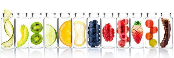 soins de la peau faits maison avec des ingrédients fruités d'avocat, d'orange, de myrtille, de grenade, de kiwi, de citron, de concombre, de tamarin, de fraise et de framboise dans des bouteilles en verre isolées sur fond blanc. photo