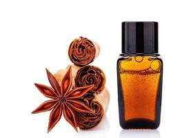 Bouteille d'huile essentielle de cannelle avec des bâtons de cannelle de Ceylan et étoile d'anis isolé sur fond blanc photo
