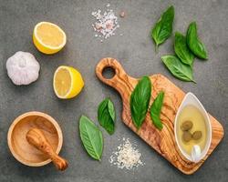 Ingrédients pour la sauce pesto maison de basilic, parmesan, ail, huile d'olive, citron et sel de l'Himalaya sur un fond de béton foncé photo
