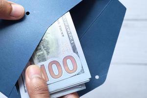personne mettant de l'argent dans une enveloppe photo