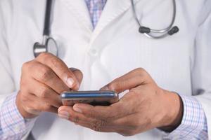 médecin en blouse blanche à l'aide d'un smartphone