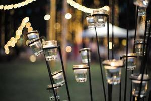 Mise au point sélective sur les bougies dans de petits verres avec des lumières floues en arrière-plan
