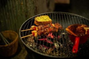 Gros plan photo de viande barbecue et pain à l'ail grillé sur le gril à charbon
