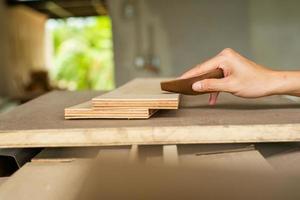 mise au point sélective sur une main de charpentier tenant du papier de verre et frotte la surface du bois photo