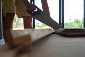 Gros plan de la main de l'homme tenant une scie manuelle et couper du bois photo