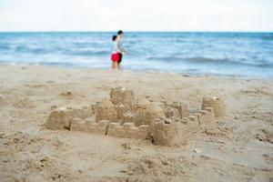 le château de sable construit en utilisant le moule avec des gens flous en arrière-plan photo