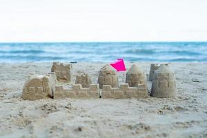 le château de sable construit en utilisant les moules en plastique sur la plage photo