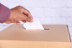 Gros plan de la main de l'homme mettant la carte dans une boîte avec fente photo