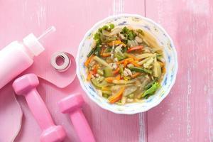 Soupe de légumes et équipement d'entraînement rose sur table photo